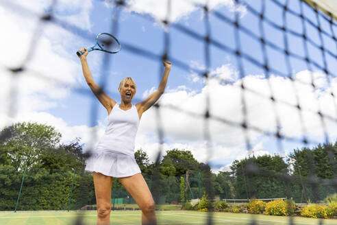 Happy female tennis player celebrating the victory on grass court - WPEF01771