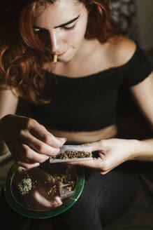 Young woman rolling a joint at home - LJF00647