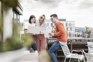 Casual business people with laptop meeting on roof terrace - UUF18547