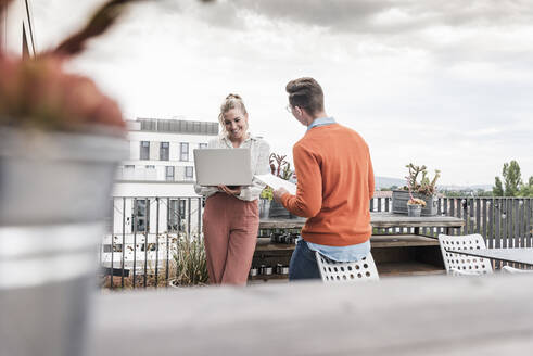 Casual businessman and woman with laptop meeting on roof terrace - UUF18550