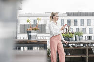 Casual businesswoman using cell phone on roof terrace - UUF18553