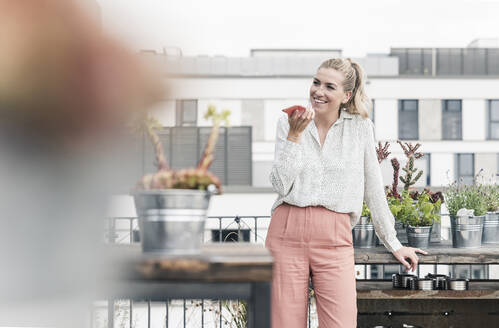 Happy casual businesswoman using cell phone on roof terrace - UUF18556