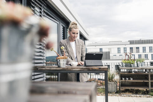 Businesswoman using tablet on roof terrace - UUF18568