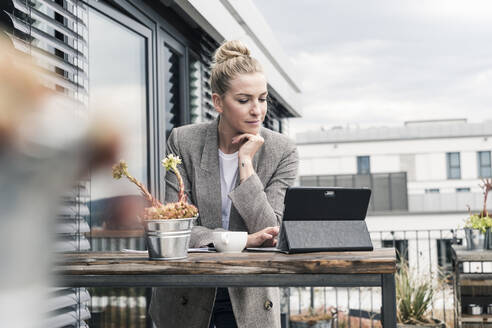 Businesswoman using tablet on roof terrace - UUF18571