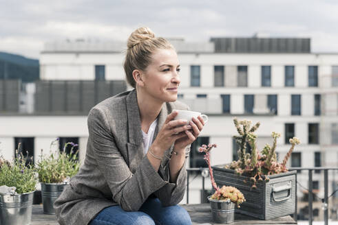 Businesswoman with coffee cup sitting on roof terrace having a break - UUF18577