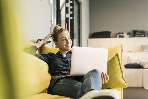 Casual businesswoman using laptop on couch in office lounge - UUF18586