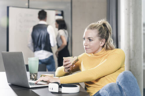 Casual businesswoman sitting at table in office using laptop and eating a sandwich - UUF18640