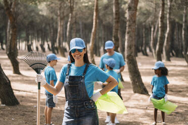 Portrait of a smiling woman with group of people collecting garbage in a park - JCMF00107