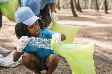 Group of volunteering children collecting garbage in a park - JCMF00110