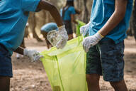 Close-up of volunteering children collecting garbage in a park - JCMF00113