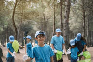 Portrait of a boy with group of people collecting garbage in a park - JCMF00116