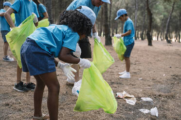 Group of volunteering children collecting garbage in a park - JCMF00119