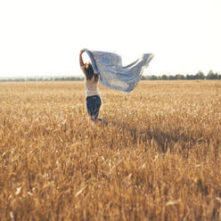 Caucasian woman carrying blanket in rural field - BLEF13918