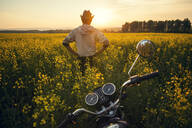 Mari man standing near motorcycle in field of flowers - BLEF14128