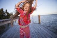 Caucasian girl dancing on pier - BLEF14161