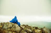 Caucasian hiker sitting on rocky hilltop - BLEF14191