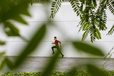 Young athlete doing intensive running training in the city - MAUF02729