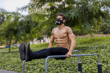 Athlete training on bars in the city, wearing breathing mask - MAUF02732