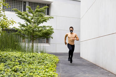 Young athlete doing intensive running training in the city, wearing breathing mask - MAUF02735
