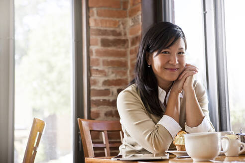 Chinese woman drinking coffee in cafe - BLEF14252