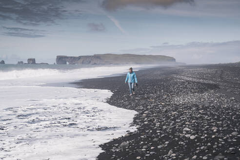Young woman walking on barefoot on a lava beach in Iceland - UUF18668