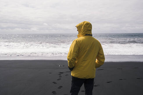 Mature man on a lava beach in Iceland, looking at the sea - UUF18674