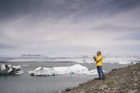Mature man watching Vatnajokull glacier with binoculars, Iceland - UUF18704