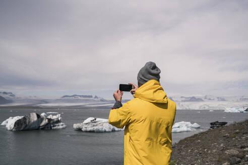 Mature man taking pictures of Vatnajokull glacier with binoculars, Iceland - UUF18710