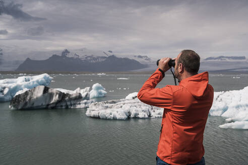 Mature man watching Vatnajokull glacier with binoculars, Iceland - UUF18719