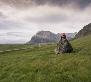 Man sitting on rock in gthe Southern Region, Iceland - UUF18722