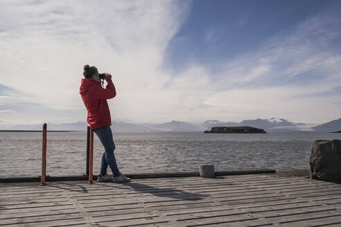 Young woman standig on a jetty, looking through binoculars, South East Iceland - UUF18728
