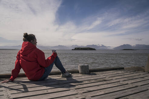Young woman sitting on a jetty, looking at the sea, South East Iceland - UUF18731