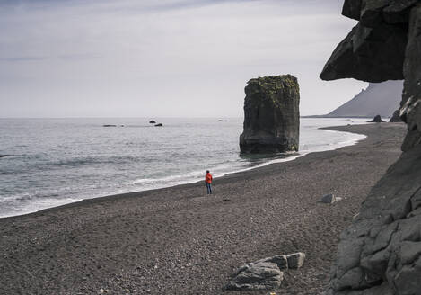 Woman on lava beach in South East Iceland, looking at the sea - UUF18737