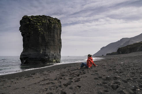 Woman on lava beach in South East Iceland, looking at the sea - UUF18740