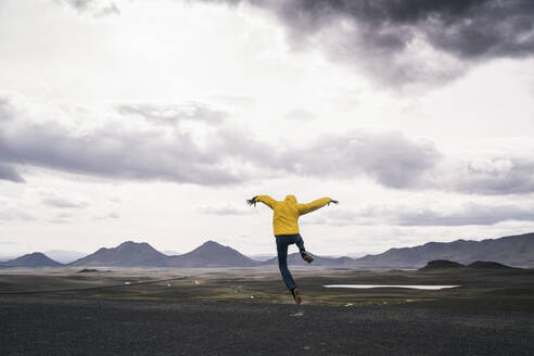 Mature man jumping for joy in the Highland Region, Iceland - UUF18749