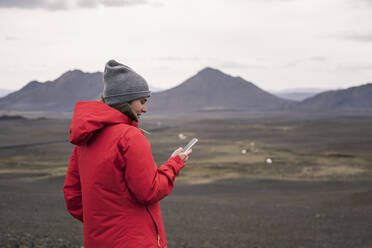 Young woman using smartphone in the Icelandic highlands - UUF18761