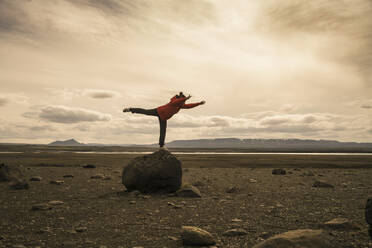 Young woman balancing on one leg on a rock in the volcanic highlands of Iceland - UUF18779