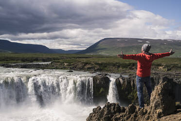 Man looking at Godafoss waterfalls, Iceland, with arms outstretched - UUF18797