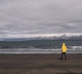 Matuer man standing on lava beach at Eyjafjordurfjord, Iceland, looking at the sea - UUF18809