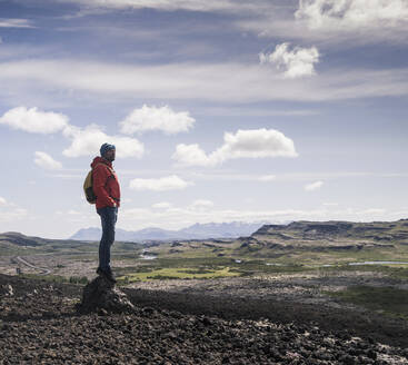 Hiker in Vesturland, Iceland, standing and looking at landscape - UUF18815