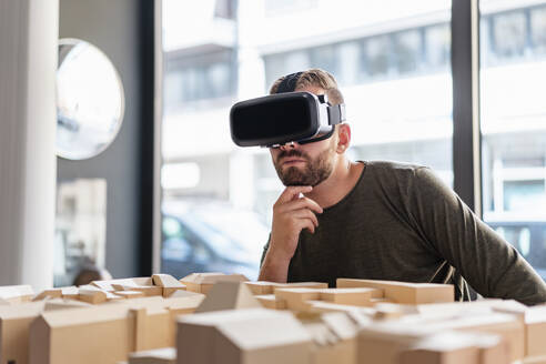 Man with architectural model in office wearing VR glasses - DIGF07913