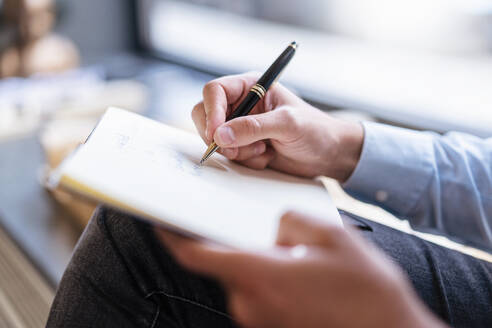 Close-up of businessman taking notes in office - DIGF07922