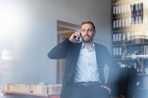 Businessman on cell phone in office - DIGF07931