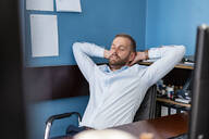 Tired businessman leaning back at desk in office - DIGF07946