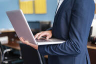 Close-up of businessman using laptop in office - DIGF07955