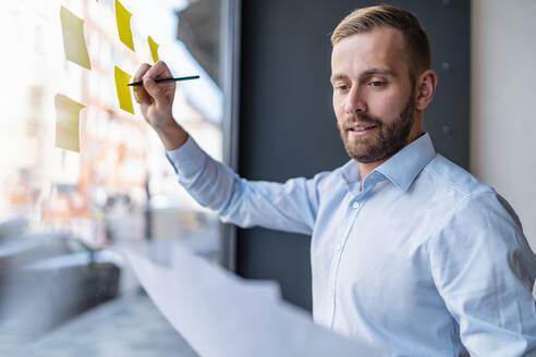 Businessman writing on adhesive notes at glass pane - DIGF07988