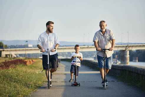 Grandfather, father and son riding scooters at the riverside - ZEDF02524
