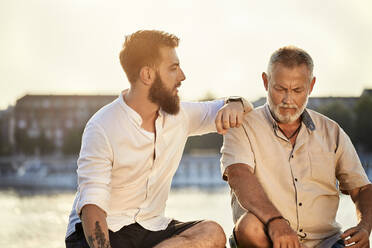 Father and adult son sitting on a wall at the riverside talking - ZEDF02530