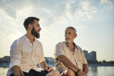 Father and adult son sitting on a wall at the riverside talking - ZEDF02533