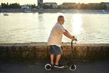 Senior man riding e-scooter at the riverside - ZEDF02536